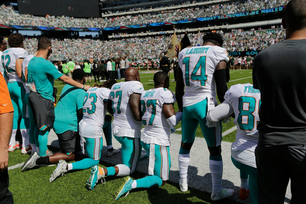 . Miami Dolphins offensive tackle Laremy Tunsil (67), Maurice Smith (27), Jarvis Landry (14) lock hands with teammates during the playing of the national anthem before an NFL football game against the New York Jets Sunday, Sept. 24, 2017, in East Rutherford, N.J. (AP Photo/Seth Wenig)