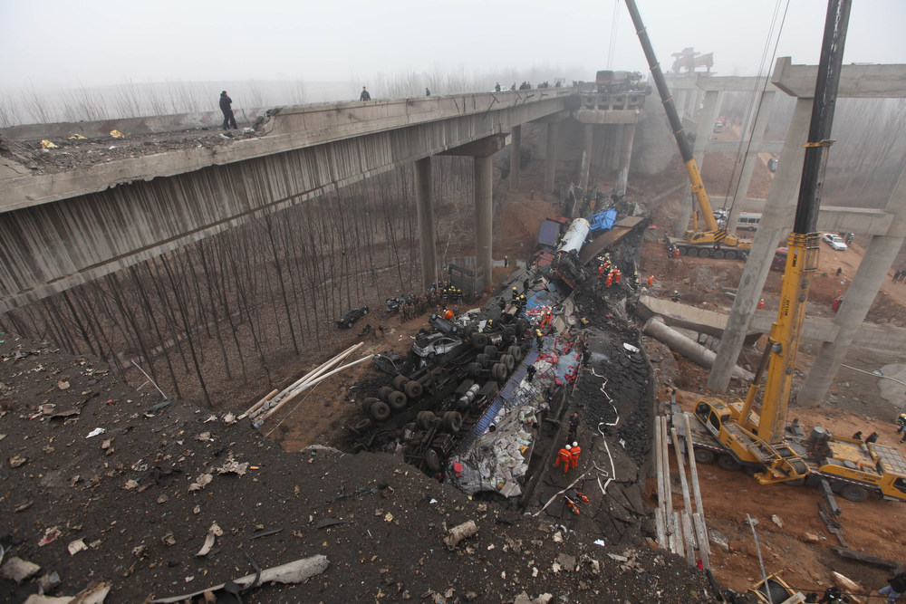 Description of . Rescuers work under the collapsed Yichang bridge near the city of Sanmenxia, central China's Henan province, on February 1, 2013. A fireworks-laden truck exploded as it crossed a bridge in central China on February 1, killing 26 people as the structure collapsed and vehicles plummeted to the ground, state-run media reported. An 80-meter long part of the bridge collapsed and six vehicles had been retrieved from the debris, China's official news agency Xinhua said. The bridge near the city of Sanmenxia is on the G30 expressway, the longest road in China, which stretches for nearly 4,400 kilometers (2,700 miles) from China's western border with Kazakhstan to the eastern Yellow Sea. AFP PHOTO    STR/AFP/Getty Images