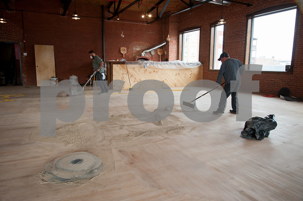 02/02/18 Wesley Bunnell | Staff David Ramirez, L, sands and Ramon Rivera sweeps up the dust from the original flooring of the building at 193 Arch St on Thursday afternoon which is the new home for Five Churches Brewery set to open soon. A brick pizza oven can be seen in the back corner.