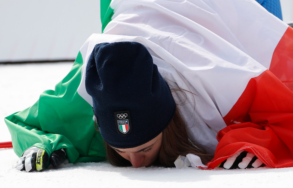 . Gold medal winner Sofia Goggia, of Italy, kisses the ground during the flower ceremony for the women\'s downhill at the 2018 Winter Olympics in Jeongseon, South Korea, Wednesday, Feb. 21, 2018. (AP Photo/Christophe Ena)