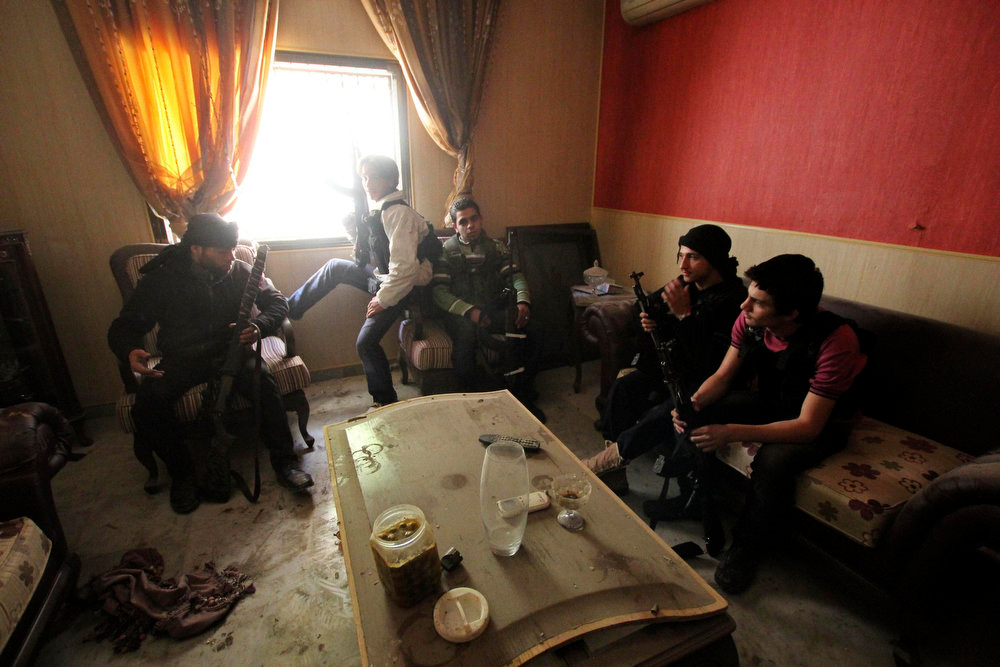 . Free Syrian Army fighters carry their weapons as they sit inside a house in Aleppo\'s Saif al-Dawla district March 20, 2013. REUTERS/Giath Taha