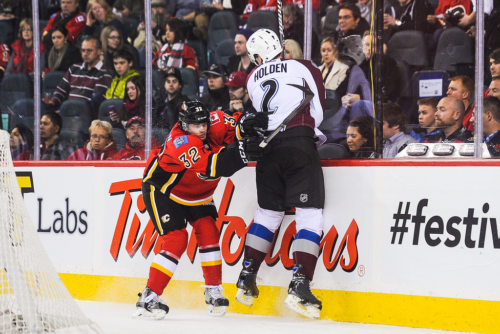 . CALGARY, AB - DECEMBER 6: Paul Byron #32 of the Calgary Flames shoves Nick Holden #2 of the Colorado Avalanche during an NHL game at Scotiabank Saddledome on December 6, 2013 in Calgary, Alberta, Canada. (Photo by Derek Leung/Getty Images)