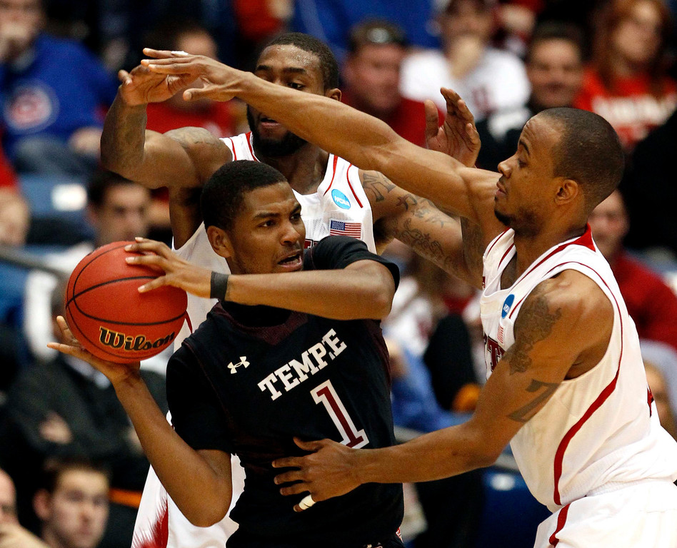 . Temple Owls guard Khalif Wyatt (1) is fouled by North Carolina State Wolfpack defenders Richard Howell (L) and Lorenzo Brown (R) during the second half of their second round NCAA tournament basketball game in Dayton, Ohio March 22, 2013. REUTERS/Matt Sullivan