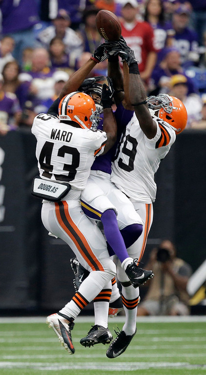 . Cleveland Browns strong safety T.J. Ward, left, and free safety Tashaun Gipson, right, break up a pass intended for Minnesota Vikings wide receiver Jerome Simpson, center, during the first half of an NFL football game Sunday, Sept. 22, 2013, in Minneapolis. (AP Photo/Jim Mone)