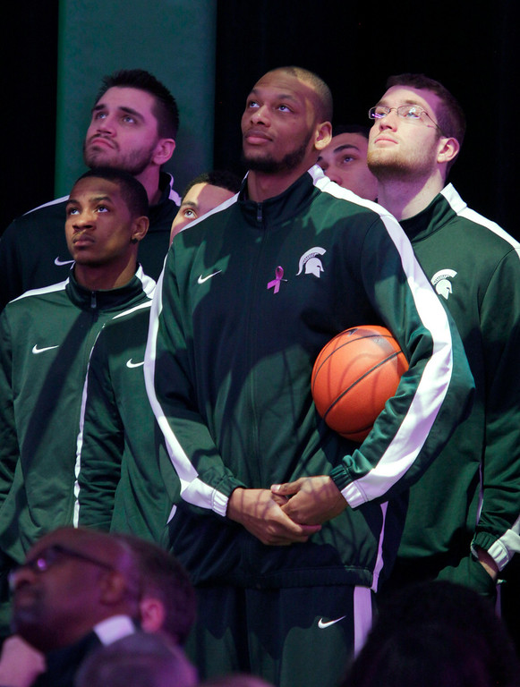 """. Members of the Michigan State basketball team, including Adreian Payne, center, Keith Appling, left, Alex Gauna, left rear, and Matt Costello, right, watch a tribute video during a memorial service for 8-year-old Lacey Holsworth, Thursday, April 17, 2014, at Michigan State University\'s Breslin Center in East Lansing, Mich. Lacey died at her home in nearby St. Johns on April 8. The little girl affectionately known as \""""Princess Lacey\"""" had neuroblastoma, a nerve-cell cancer. She wore a blond wig because chemotherapy took her hair. (AP Photo/Al Goldis)"""