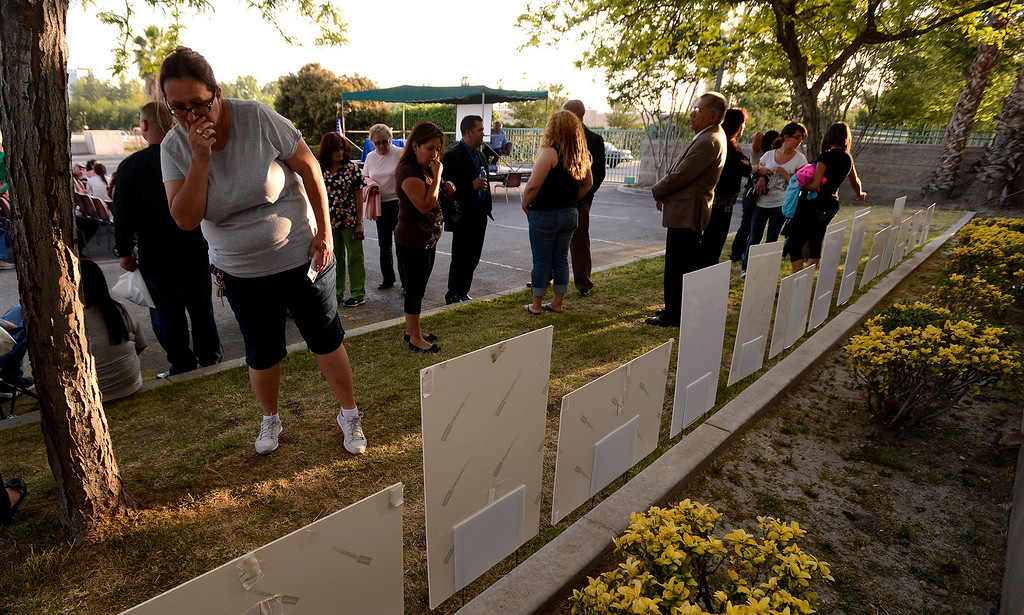 . People view a row of posters commemorating the lives of homicide victims during the annual Victims Candlelight Vigil at the police station in San Bernardino April 23, 2013.   GABRIEL LUIS ACOSTA/STAFF PHOTOGRAPHER.
