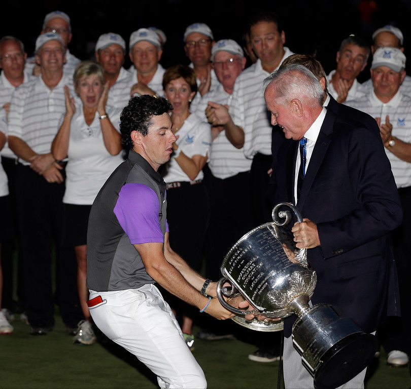 . Rory McIlroy, of Northern Ireland, catches the Wanamaker Trophy from PGA of America president Ted Bishop after winning the PGA Championship golf tournament at Valhalla Golf Club on Sunday, Aug. 10, 2014, in Louisville, Ky. (AP Photo/David J. Phillip, File)