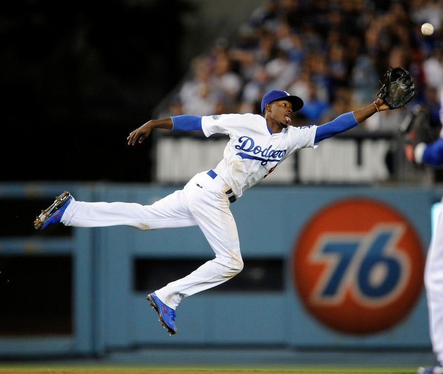 . The Dodgers\' Dee Gordon (9) comes up short on an attempt to catch a short fly ball hit by the Mets\' Ruben Tejada (11) in the 7th inning during their game at Dodger Stadium Friday, June 29, 2012. (Hans Gutknecht/Staff Photographer)