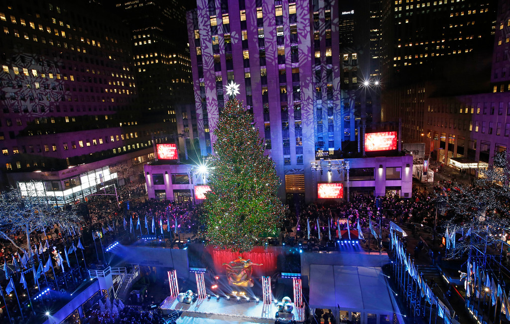 . The Rockefeller Center Christmas tree is lit following a ceremony, Wednesday, Dec. 4, 2013, in New York. Some 45,000 energy efficient LED lights adorn the 76-foot tree. (AP Photo/Kathy Willens)