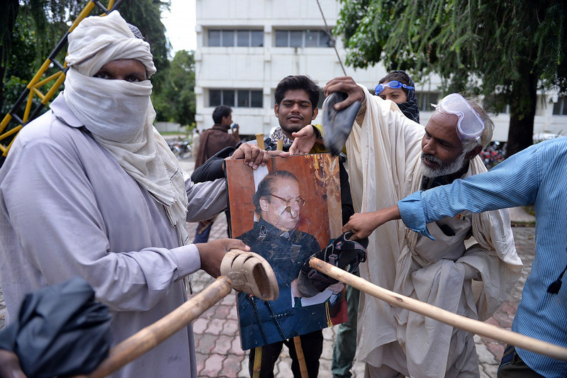 . Pakistani supporters of Canadian cleric Tahir ul Qadri and cricket-turned politician Imran Khan beat a photograph of Prime Minister Nawaz Sharif with sandals after storming the headquarters of the state-owned Pakistani Television (PTV) building during anti-government protest in Islamabad on September 1, 2014. Hundreds of protesters trying to topple Pakistan\'s government stormed the state broadcaster on September 1 as fresh clashes with police broke out in Islamabad. AAMIR QURESHI/AFP/Getty Images