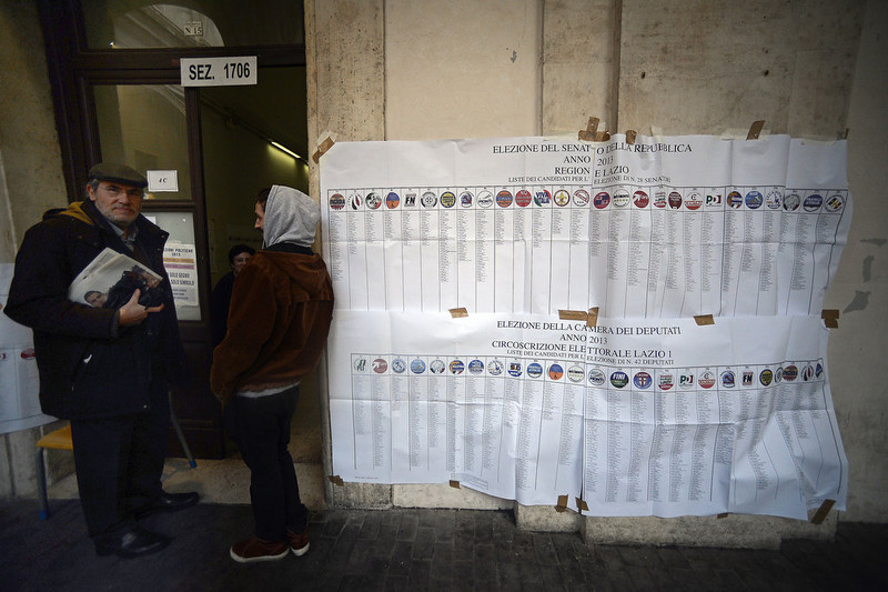 . Men stand by electoral banners before voting at a polling station in downtown Rome on February 24,2013, as part of  Italy\'s general elections. The centre-left is the favourite of this vote, as Europe held its breath for signs of fresh instability in the eurozone\'s third economy.   FILIPPO MONTEFORTE/AFP/Getty Images