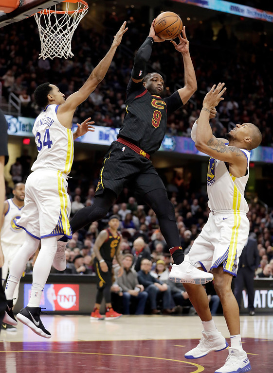 . Cleveland Cavaliers\' Dwyane Wade (9) passes against Golden State Warriors\' Shaun Livingston (34) and David West (3) in the first half of an NBA basketball game, Monday, Jan. 15, 2018, in Cleveland. (AP Photo/Tony Dejak)