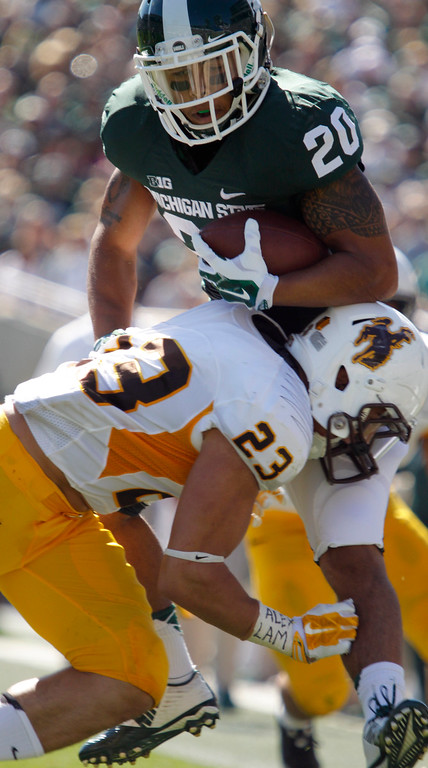 . Michigan State\'s Nick Hill (20) is stopped by Wyoming\'s Tom Kamana (23) during the second quarter of an NCAA college football game, Saturday, Sept. 27, 2014, in East Lansing, Mich. (AP Photo/Al Goldis)