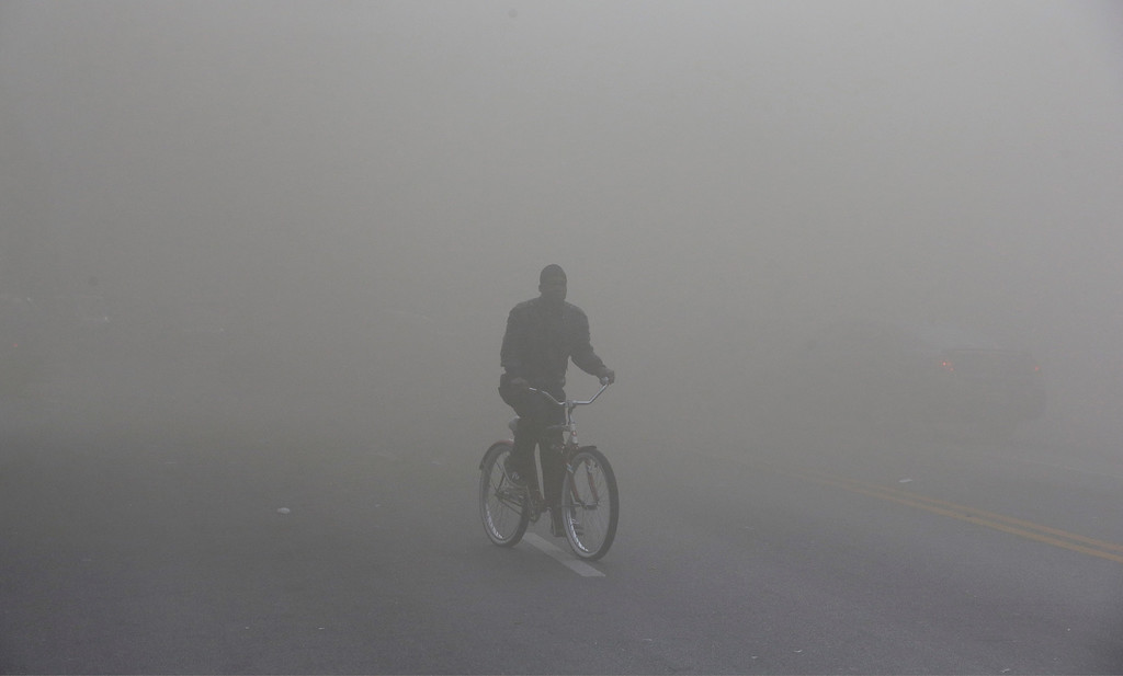 . A man rides a bicycle through heavy smoke that is emitting from a nearby store on fire, Monday, April 27, 2015, during unrest following the funeral of Freddie Gray in Baltimore. (AP Photo/Patrick Semansky)