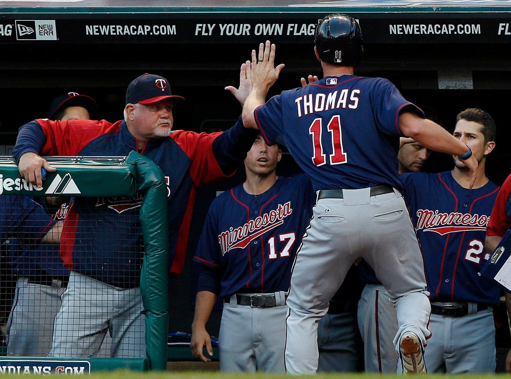 . Minnesota\'s Clete Thomas is greeted by manager Ron Gardenhire as he returns to the dugout after scoring on an RBI double by Pedro Florimon during the second inning.   (Photo by David Maxwell/Getty Images)