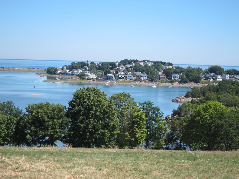 Green trees and lawn on World's End look out onto blue water and Hull, an island near Boston