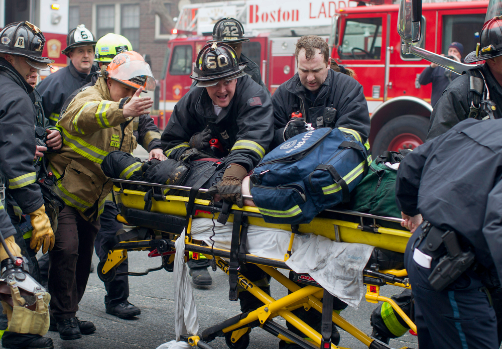 . Firefighters and emergency medical personnel rush a firefighter from the scene of a multi-alarm fire at a four-story brownstone in the Back Bay neighborhood near the Charles River, Wednesday, March 26, 2014, in Boston. Boston EMS spokesman Nick Martin says four people, including at least three firefighters, have been taken to hospitals. (AP Photo/Scott Eisen)