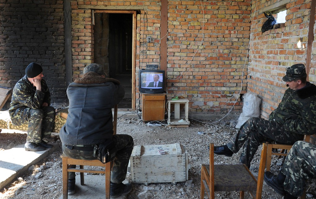 . Ukrainian pilots watch TV displaying Russian President Vladimir Putin\'s speach as they sit in an unfinished building at the Belbek air -base not far from the Crimean city of Sevastopol on March 21, 2014. Surly and dejected, many Ukrainian soldiers at Perevalne base in Crimea deserted their posts Friday, crossing groups of buoyant Russian soldiers moving in -- but 200 were said to be resisting. Overwhelmed by superior force and on the day Russia formally claimed the Black Sea peninsula as its territory, the biggest base still holding out against a creeping month-long invasion was slowly giving up.  AFP PHOTO/ VIKTOR DRACHEV/AFP/Getty Images
