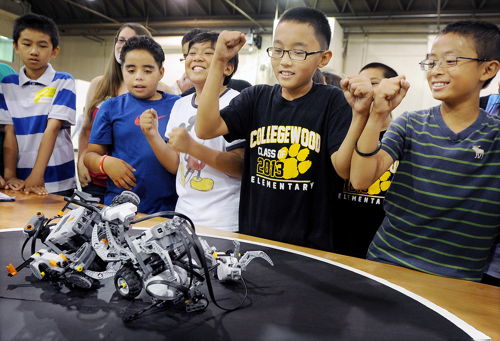 """. Cal Poly Pomona\'s Robotics Initiative invited 200 elementary and middle school students to a Robot Expo at LA Fairplex in Pomona Monday, May 20, 2013.  William Go, third from left, Nathan Leung, and Tyler Xu of Collegewood Elementary from Walnut Valley, cheering for their teams robot named \""""Exterminators\"""", over its rival during contest. Evergreen Elementary finished second in the competition. (SGVN/Photo by Walt Mancini)"""
