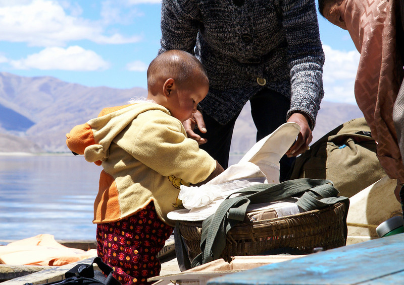 Small Tibetan boy inspecting goods on ferry.