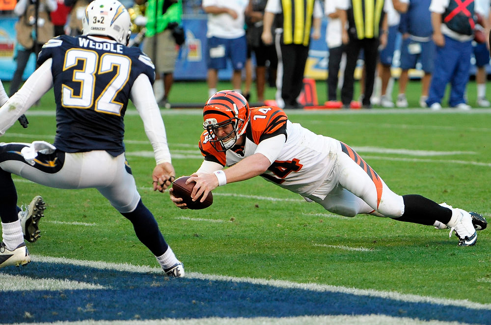 Description of . Cincinnati Bengals quarterback Andy Dalton, right, dives into the end zone for a touchdown against the San Diego Chargers during the second half of an NFL football game, Sunday, Dec. 2, 2012, in San Diego. (AP Photo/Denis Poroy)