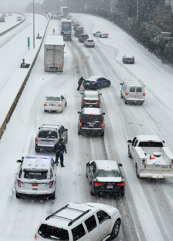 . Traffic along Independence Boulevard near Hawthorne Lane crawls along the slick roadway as a winter storm hits   Wednesday, Feb. 12, 2014, in Charlotte, N.C. (AP Photo/The Charlotte Observer, Davie Hinshaw)