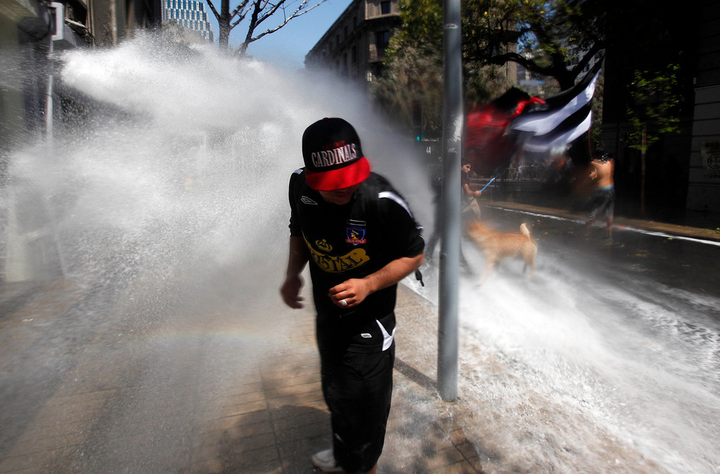 . A protester runs away from a police water cannon after clashes broke out at a march against the commemoration of the discovery of America in Santiago, Chile, Saturday, Oct. 12, 2013. The march was organized by members of indigenous groups demanding autonomy and the recovery of ancestral land. Protesters also demonstrated against Chile\'s anti-terrorism law, under which many Mapuche Indians are under arrest. Saturday is the the anniversary of Christopher Columbus\' 1492 arrival in the Americas. (AP Photo/Luis Hidalgo)