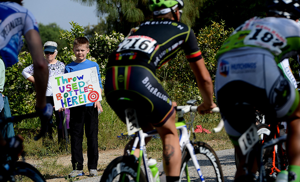 . Daniel Krall, 13, of Colton attempts to get riders water bottles Sunday April 7, 2013 during the Redlands Bicycle Classic. Crowds of spectators gather along the streets of Redlands for the final day of the 29th Annual Redlands Bicycle Classic. Rick Sforza/Staff photographer
