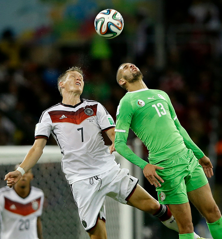 . Germany\'s Bastian Schweinsteiger, left, heads the ball against Algeria\'s Islam Slimani during the World Cup round of 16 soccer match between Germany and Algeria at the Estadio Beira-Rio in Porto Alegre, Brazil, Monday, June 30, 2014. (AP Photo/Kirsty Wigglesworth)