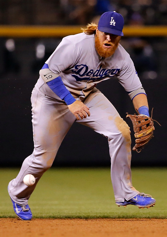 . Los Angeles Dodgers\' Justin Turner misses a ground ball hit by Colorado Rockies\' Justin Morneau during the sixth inning of a baseball game Tuesday, Sept. 16, 2014, in Denver. (AP Photo/Jack Dempsey)