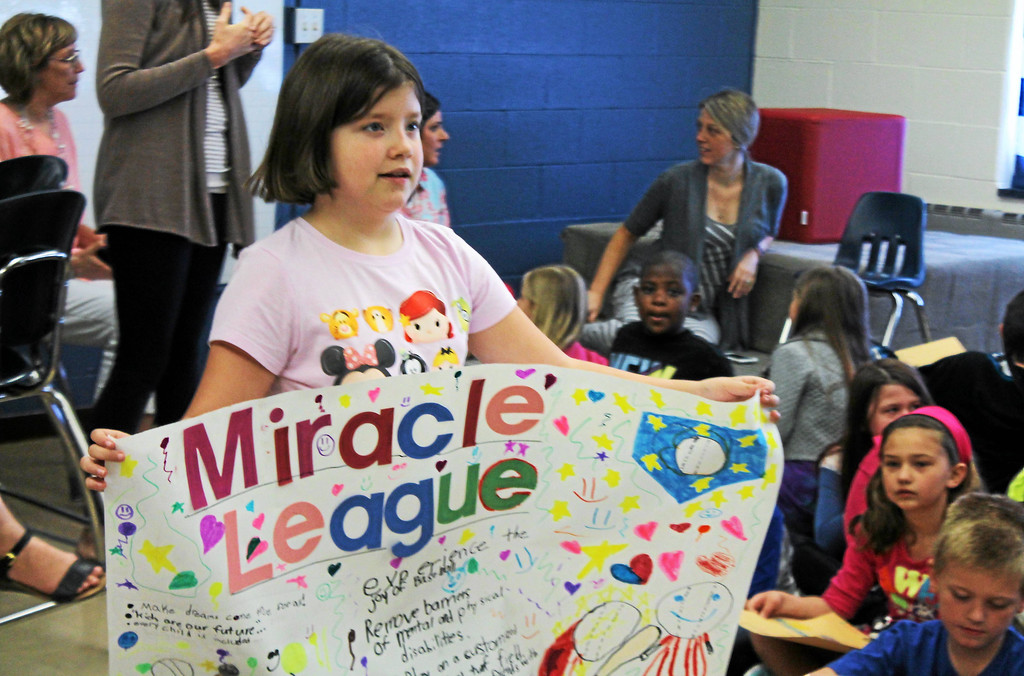 . Kristi Garabrandt � The News-Herald <br> Sidney Sobochan, second grade student at Longfellow Elementary Schools, carries one of the posters the second grade class worked on  as a project based learning experience to help promote The Miracle League of Lake County.