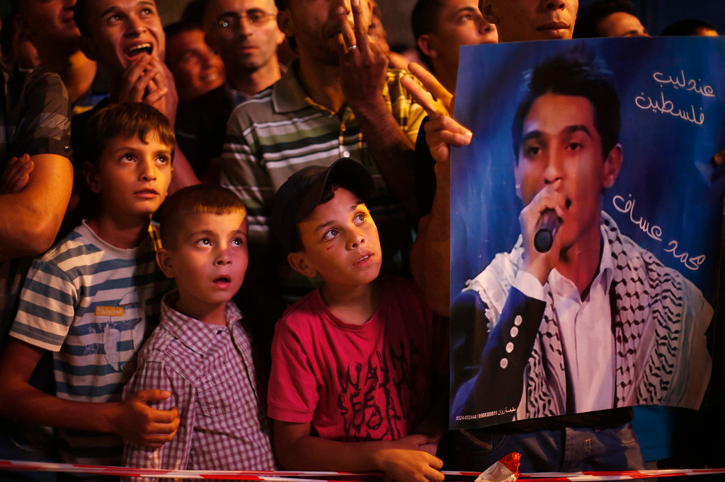 ". A Palestinian holds a poster of singer Mohammed Assaf as the crowd watch the result of ""Arab Idol\"" in the West Bank city of Ramallah on June 22, 2013. The 22-year-old singer Mohammed Assaf, from the Gaza Strip, was named the winner of \""Arab Idol\"" in a TV talent contest in Beirut. REUTERS/Mohamad Torokman"