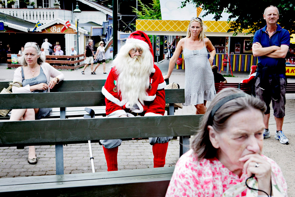Description of . A lone Santa sits in the Dyrehavsbakken amusement park, north of Copenhagen, Denmark, Monday, July 19, 2010 where many have gathered for the World Santa Claus Congress, which has been held 52 times now at the amusement park, which is popularly known just as Bakken.  Every summer, Santas from the entire world get together at Bakken to spread some Christmas cheer, have fun, and enjoy a get-together. The congress, held in July because all of the Santa\'s are very busy in December, attracts as many as 200 Santas and Elves, and audiences of many thousands.  (AP Photo/Polfoto, Nanna Kreutzmann)