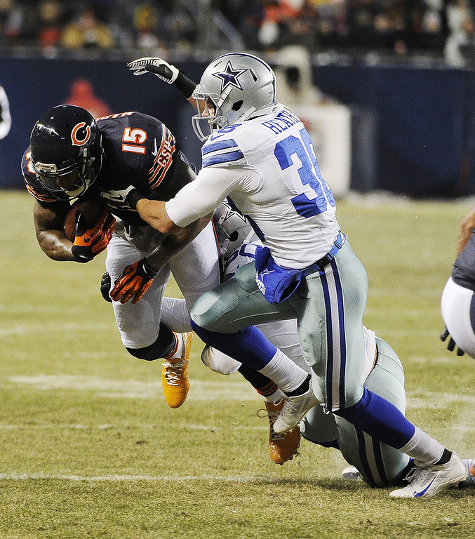 . Brandon Marshall #15 of the Chicago Bears is tackled by Orlando Scandrick #32 of the Dallas Cowboys during the first quarter on December 9, 2013 at Soldier Field in Chicago, Illinois. (Photo by David Banks/Getty Images)