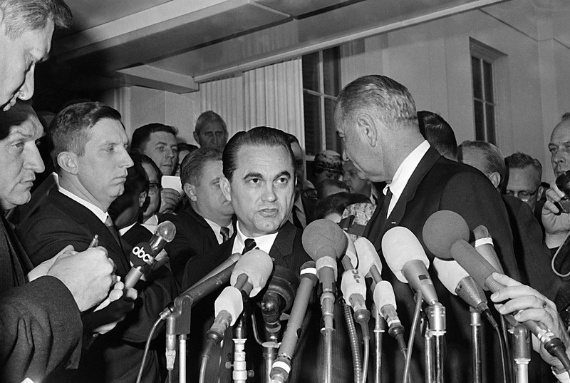 . Alabama Gov. George Wallace, left at the microphone, stands with Pres. Lyndon Johnson, right, as he talks to reporters outside the White House office wing, March 13, 1965, Washington, D.C. After the conference of more than three hours, they told newsmen each had made recommendations to the other for dealing with racial tensions in Selma, Ala.  (AP Photo)