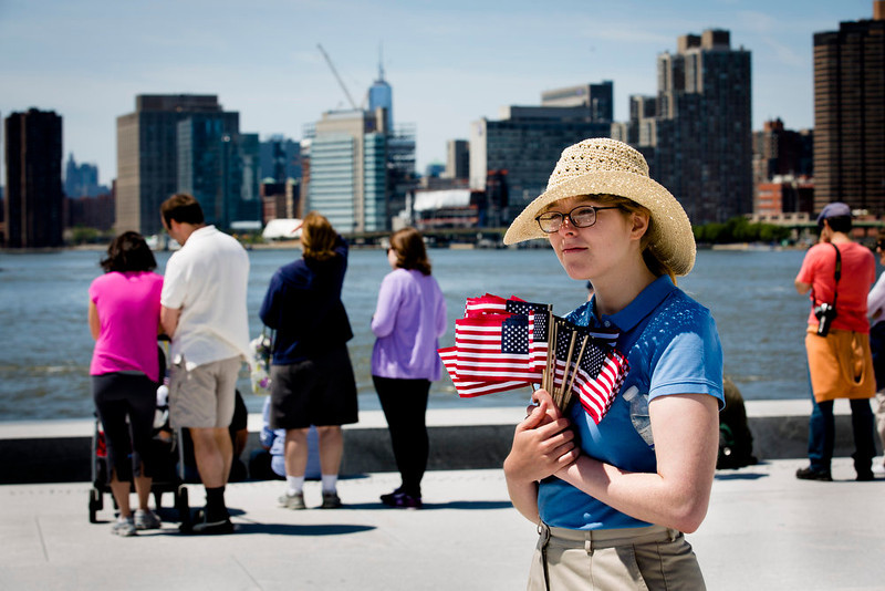 . Park ranger Victoria Thompson holds American flags as visitors view the Manhattan skyline after a Memorial Day wreath laying at the Franklin D. Roosevelt Four Freedoms Park on Roosevelt Island, Monday, May 27, 2013, in New York. (AP Photo/John Minchillo)