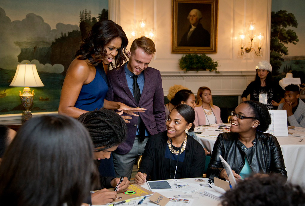 """. First lady Michelle Obama visits the \""""Wearable Technology\"""" workshop with workshop leader Cody Miller, standing right, who is introducing the participants during the wearable technology and basic electronics, Wednesday, Oct. 8, 2014, in the Diplomatic Room of the White House in Washingto, during the Fashion Education Workshop. Wearable technology is the integration of technology with fashion, like boots that charges cellphone, bras that detect cancer, compression shirts that monitor and record your heart rate, breathing rate and body temperature, etc.  (AP Photo/Manuel Balce Ceneta)"""