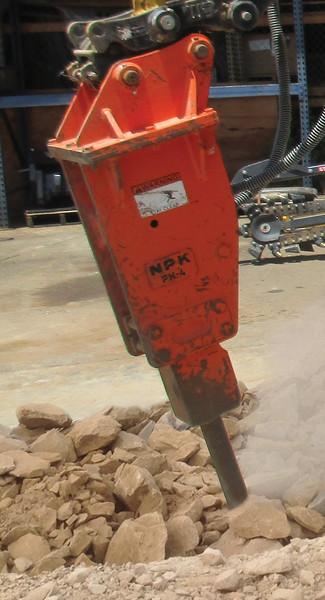 NPK PH4 hydraulic hammer with standard bracket breaking rock.jpg