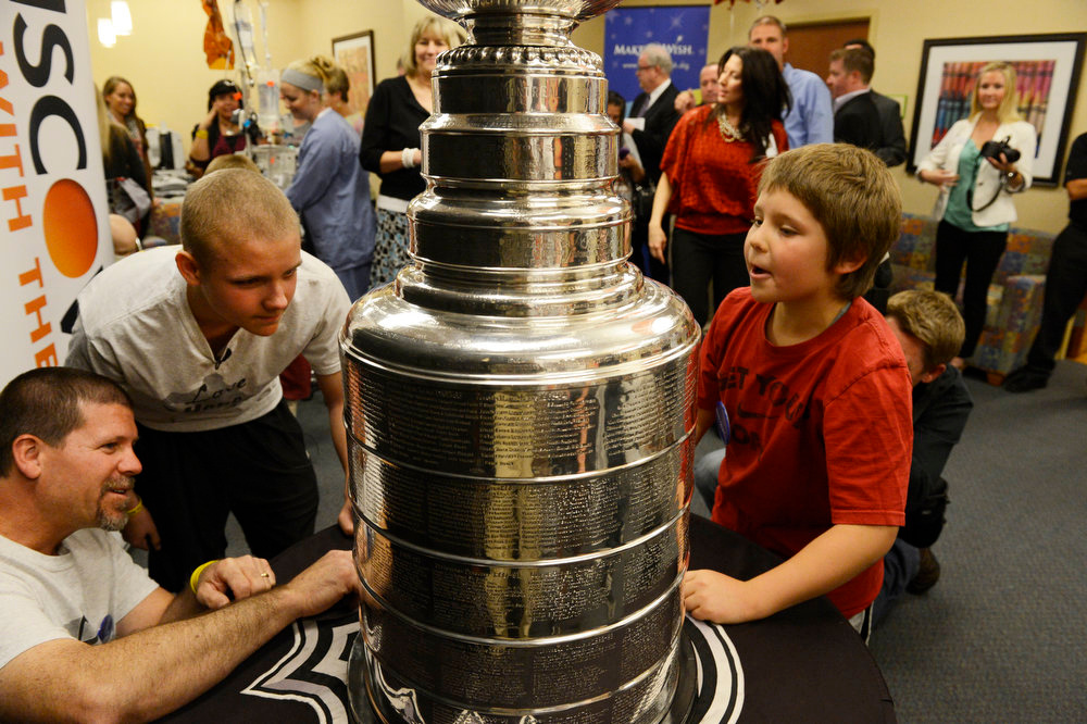 . Logan (l-r) Ron Piz and his sons, Logan, 13, and Hayden, 9, admire  the Stanley Cup at Rocky Mountain Hospital for Children in Denver, CO on May 15, 2013. The hospital, Make-A-Wish, Discover and the National Hockey League teamed up to grant  Logan\'s wish to spend a day with the Stanley Cup and share it with friends, family and supporters. Logan has not played hockey since he was diagnosed with Ewing�s sarcoma in November 2012.(Photo By Craig F. Walker/The Denver Post)