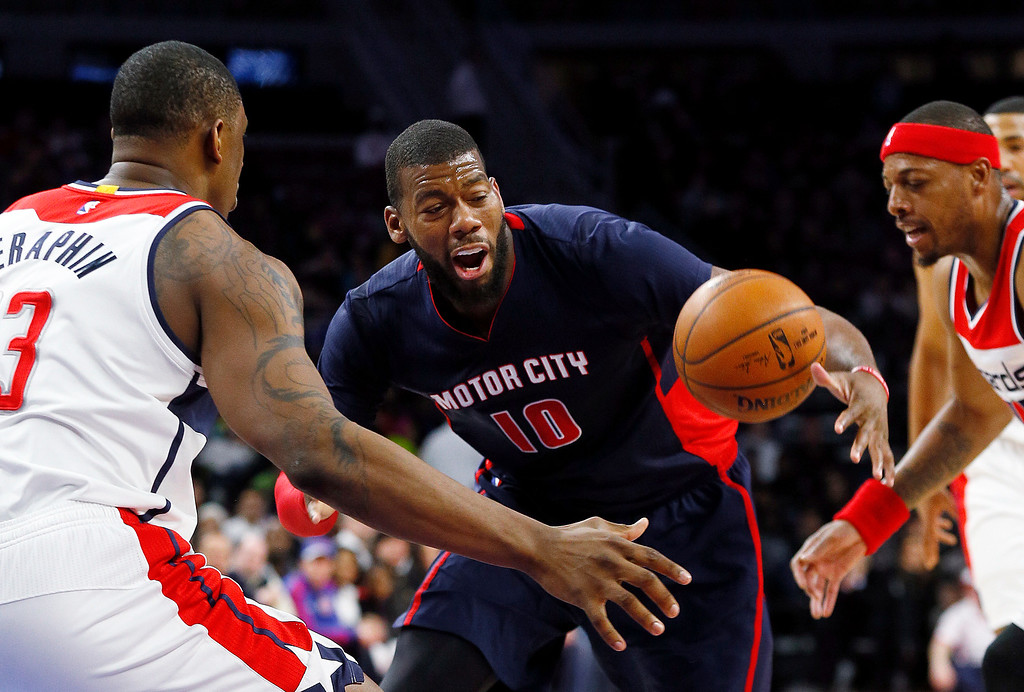 . Detroit Pistons forward Greg Monroe (10) looses the ball as Washington Wizards center Kevin Seraphin (13) and Washington Wizards forward Paul Pierce, right, defend in the first half of an NBA basketball game in Auburn Hills, Mich., Sunday, Feb. 22, 2015. (AP Photo/Paul Sancya)