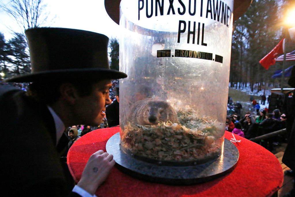 . Groundhog Club inner circle member Dan McGinley, left, visits with Punxsutawney Phil, the weather prognosticating groundhog, during the 131st celebration of Groundhog Day on Gobbler\'s Knob in Punxsutawney, Pa. Thursday, Feb. 2, 2017. Phil\'s handlers said that the groundhog has forecast six more weeks of winter weather. (AP Photo/Gene J. Puskar)
