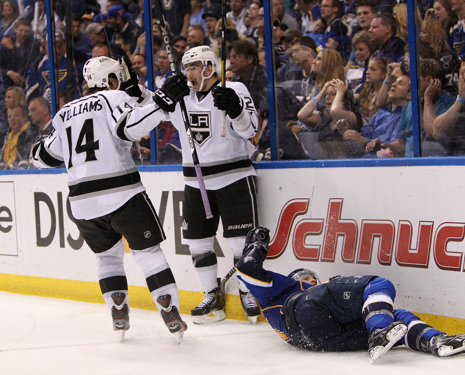 . Los Angeles defenseman Slava Voynov, center, celebrates with teammate Justin Williams after scoring the game-winning goal in overtime during Game 5 of the Western Conference quarterfinals between the St. Louis Blues and the Los Angeles Kings on Wednesday, May 8, 2013, at the Scottrade Center in St. Louis.  At right is Blues left wing Jaden Schwartz. (AP Photo/St. Louis Post-Dispatch, Chris Lee)
