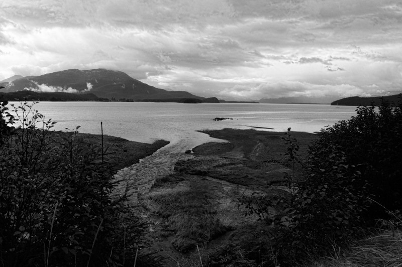 12 Mar 13.Driving around the greater Juneau area last September I passed numerous little curves in the land which had bodies of water associated with them and each, I'm rather certain, if anything like the peninsula on which we reside, had its unique name. Unfortunately I failed to see most of them and that includes the image for today. In the original there was a rather interesting play of red and green color on the patch of land at the bottom of the scene where the creek enters the bay, as well as some foreboding clouds. It was the contrast of the clouds against the strip of color that caught my eye. But as much as I liked the color, I like it even better in monochrome, so it became this week's entry for B&W Tuesday. I've brought out the detail in the clouds just a bit, and of course converted it to B&W, otherwise, this is how it looked on a cold, windy, temporarily rain free morning. D800; 18 - 200; Aperture Priority; ISO 200; 1/400 sec @ f /8.