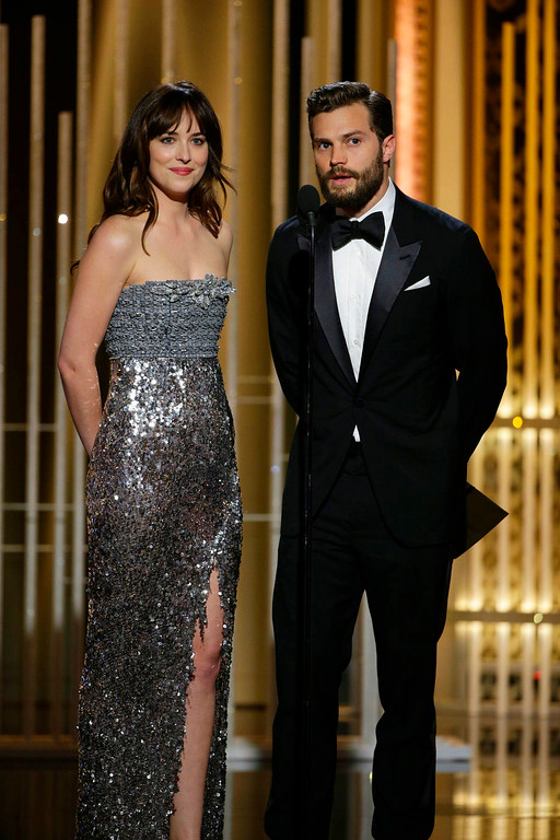 . In this image released by NBC, Dakota Johnson, left, and Jamie Dornan present an award at the 72nd Annual Golden Globe Awards on Sunday, Jan. 11, 2015 at the Beverly Hilton Hotel in Beverly Hills, Calif. (AP Photo/NBC, Paul Drinkwater)