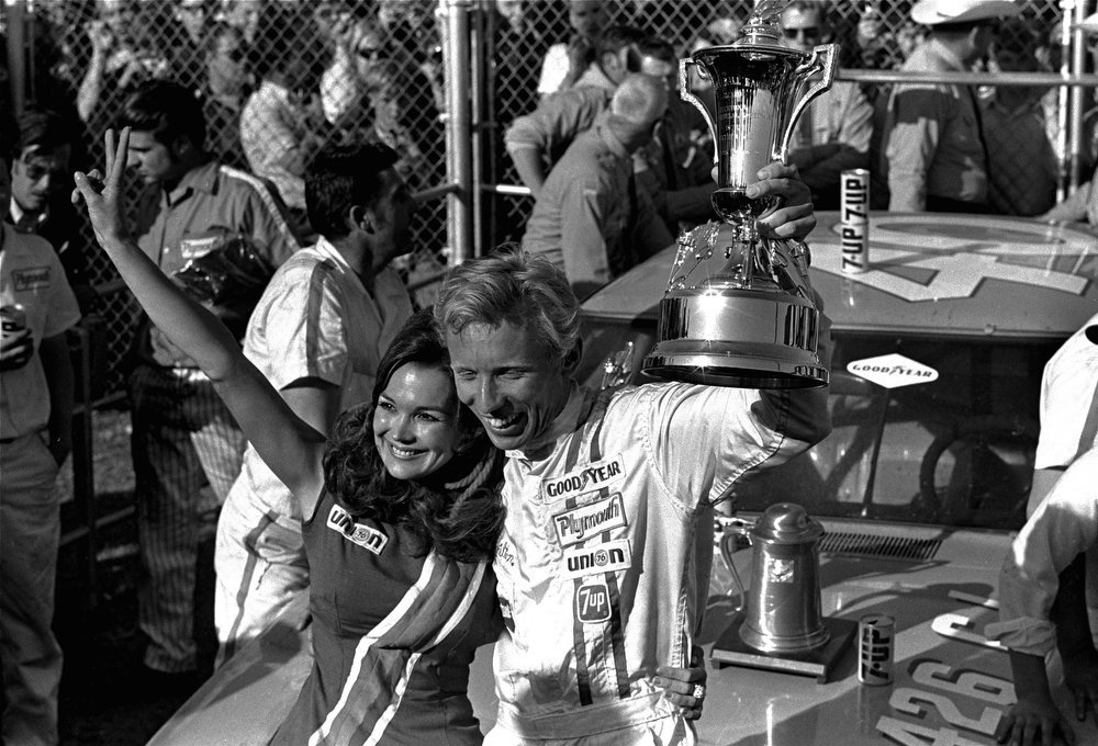 Description of . Pete Hamilton, Charlotte, NC, waves a trophy and Sharon Brown waves in victory lane after Hamilton won the Daytona 500 at Daytona Beach, Fla. Sunday, February 23, 1970.  Hamilton drove a 1970 Plymouth and eked out a victory over second place winner David Pearson who was driving a 1969 Ford. (AP Photo/CS)