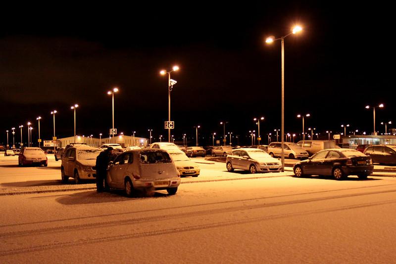 © Marta Popovics 20-12-2009 Tirando o gelo do vidro do carro no estacionamento do aeroporto, na chegada das férias.