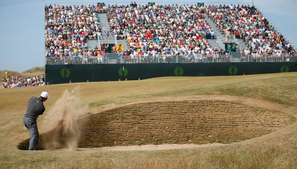 . Tiger Woods of the United States plays a shot out of the bunker on the 4th hole during the third round of the British Open Golf Championship at Muirfield, Scotland, Saturday July 20, 2013. (AP Photo/Peter Morrison)