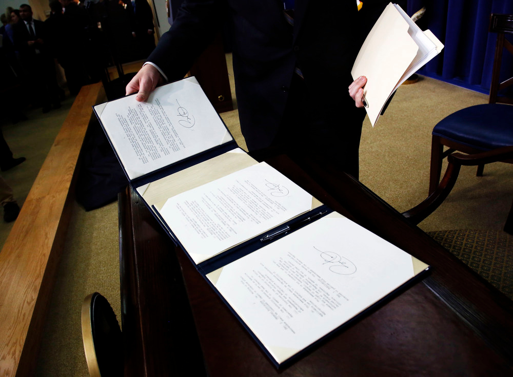 . An aide collects binders with the executive orders on gun violence that President Barack Obama signed immediately after a signing ceremony in which Obama implemented a series of proposals to counter gun violence during an event at the  White House in Washington, January 16, 2013. Vice President Joe Biden delivered his recommendations to Obama after holding a series of meetings with representatives from the weapons and entertainment industries as requested by the president after the December 14 school shooting in Newtown, Connecticut, in which 20 children and six adults were killed. REUTERS/Jason Reed