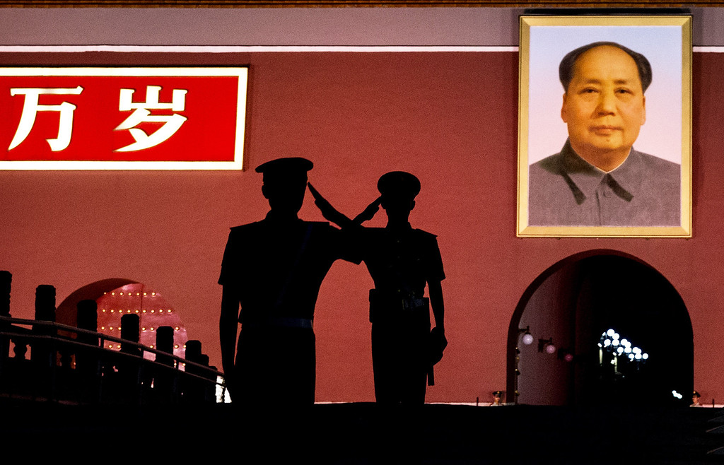 . Chinese Paramilitary police officers salute each other as they stand guard below a portrait of the late leader Mao Zedong in Tiananmen Square on June 4, 2014 in Beijing, China. (Photo by Kevin Frayer/Getty Images)