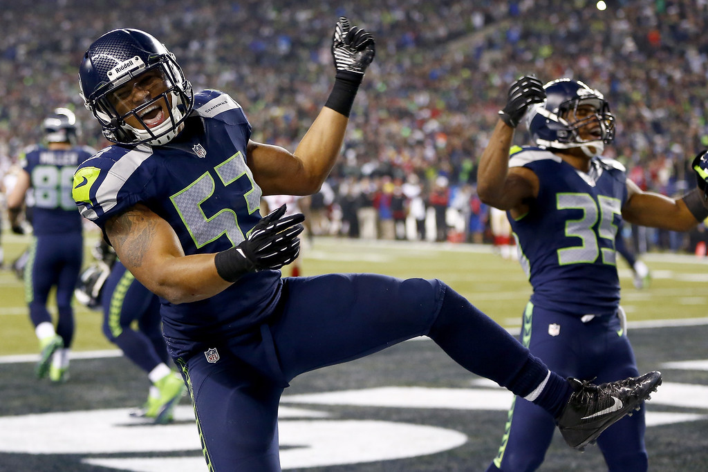 . Outside linebacker Malcolm Smith #53 and defensive back DeShawn Shead #35 celebrate after Smith intercepts a pass in the endzone to win the game for the Seahawks against the San Francisco 49ers during the 2014 NFC Championship at CenturyLink Field on January 19, 2014 in Seattle, Washington.  (Photo by Jonathan Ferrey/Getty Images)
